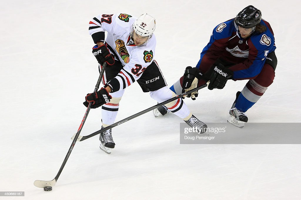 Brandon Pirri #37 of the Chicago Blackhawks controls the puck against Nate Guenin #5 of the Colorado Avalanche at Pepsi Center on November 19, 2013 in Denver, Colorado. The Avalacnhe defeated the Blackhawks 5-1.