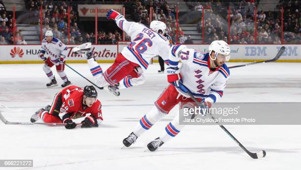 Brandon Pirri of the New York Rangers skates with the puck as teammate Jimmy Vesey jumps over a fallen JeanGabriel Pageau of the Ottawa Senators in...