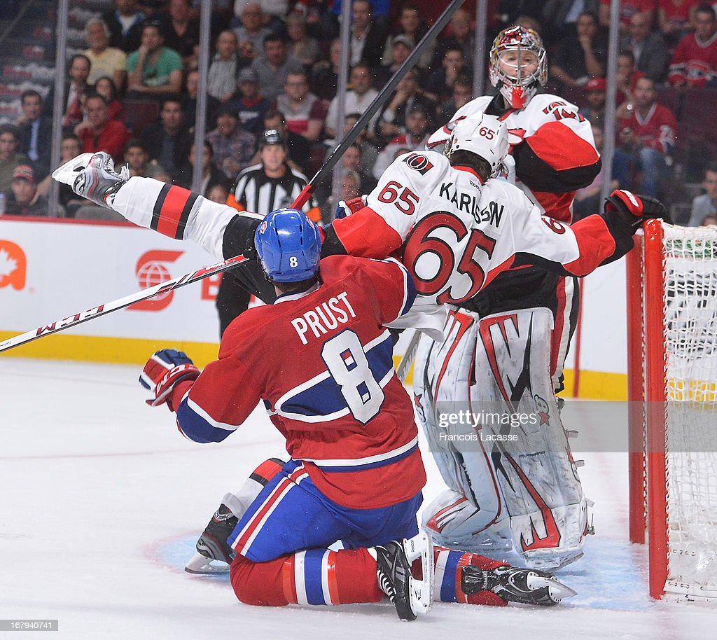 <a gi-track='captionPersonalityLinkClicked' href=/galleries/search?phrase=Brandon+Prust&family=editorial&specificpeople=2221796 ng-click='$event.stopPropagation()'>Brandon Prust</a> #8 of the Montreal Canadiens collides with <a gi-track='captionPersonalityLinkClicked' href=/galleries/search?phrase=Erik+Karlsson&family=editorial&specificpeople=5370939 ng-click='$event.stopPropagation()'>Erik Karlsson</a> #65 of the Ottawa Senators in front of the goal in Game One of the Eastern Conference Quarterfinals during the 2013 NHL Stanley Cup Playoffs at the Bell Centre on May 2, 2013 in Montreal, Quebec, Canada.