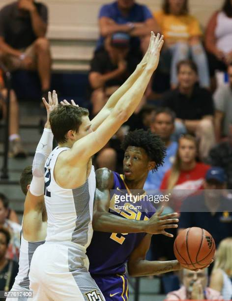 Brandon Rachal of the LSU Tigers is double teamed by Matt Heldt and Andrew Rowsey of the Marquette Golden Eagles during the first half of their game...