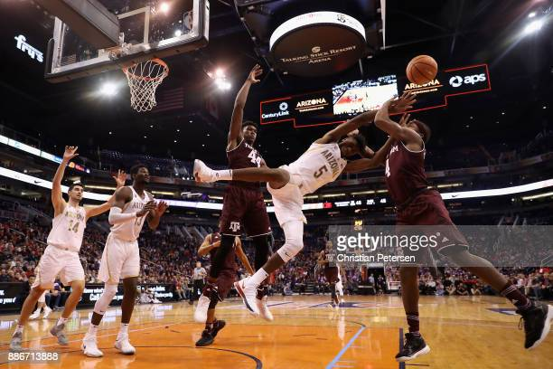 Brandon Randolph of the Arizona Wildcats is fouled as he drives to the basket against Robert Williams and JJ Caldwell of the Texas AM Aggies during...