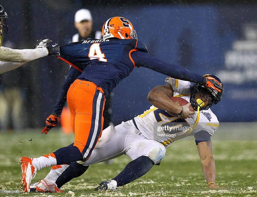 Brandon Reddish #4 of the Syracuse Orange reaches to tackle Shawne Alston #20 of the West Virginia Mountaineers during the New Era Pinstripe Bowl at Yankee Stadium on December 29, 2012 in the Bronx borough of New York City.