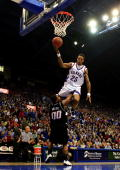 Brandon Rush of the Kansas Jayhawks leaps over Byron Eaton of the Oklahoma State Cowboys to score during the first half of the game on January 10...