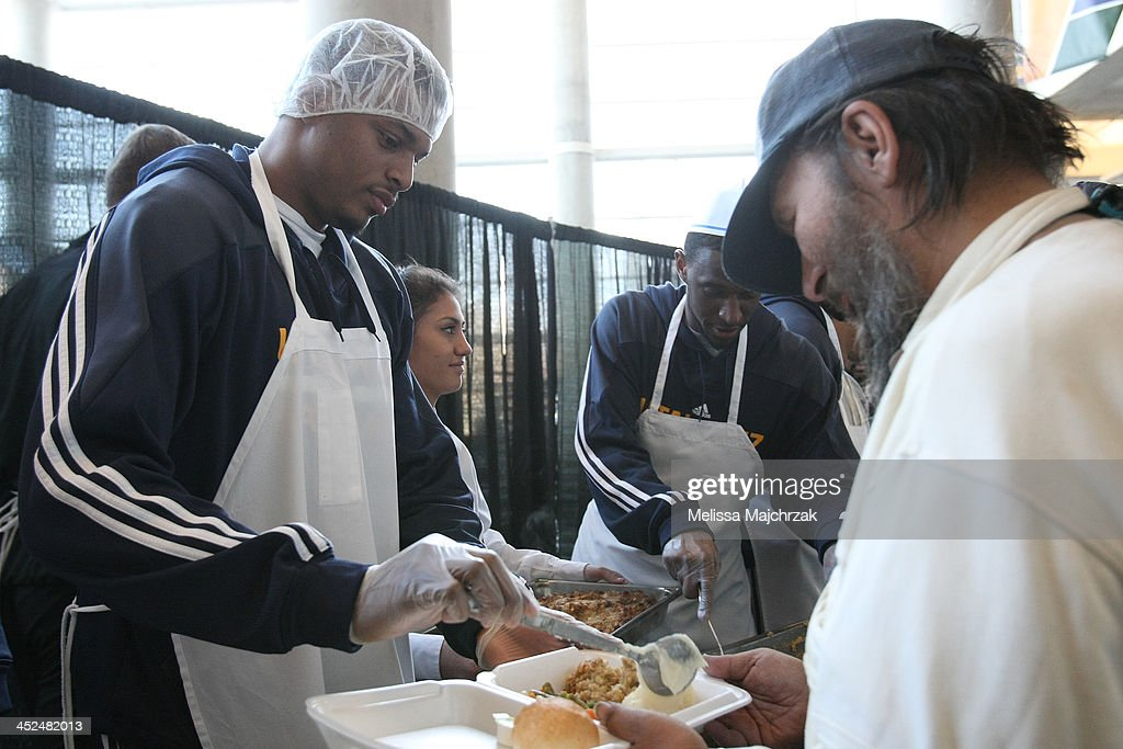 Brandon Rush #25 of the Utah Jazz dishes out food during the we care-we share Thanksgiving Dinner feeding the homeless at EnergySolutions Arena on November 27, 2013 in Salt Lake City, Utah.