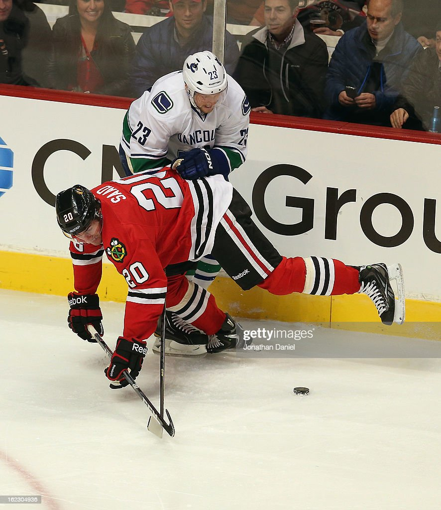 Brandon Saad #20 of the Chicago Blackhawks and <a gi-track='captionPersonalityLinkClicked' href=/galleries/search?phrase=Alexander+Edler&family=editorial&specificpeople=882987 ng-click='$event.stopPropagation()'>Alexander Edler</a> #23 of the Vancouver Canucks battle for the puck at the United Center on February 19, 2013 in Chicago, Illinois. The Blackhawks defeated the Canucks 4-3 in a shootout.