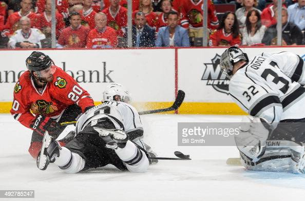 Brandon Saad of the Chicago Blackhawks and Drew Doughty of the Los Angeles Kings get physical in front of goalie Jonathan Quick of the Kings in Game...