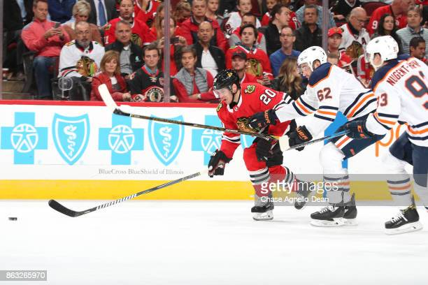 Brandon Saad of the Chicago Blackhawks and Eric Gryba of the Edmonton Oilers chase the puck in the second period at the United Center on October 19...