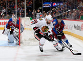 Brandon Saad of the Chicago Blackhawks and Zach Redmond of the Colorado Avalanche battle for control of the puck as goalie Calvin Pickard of the...