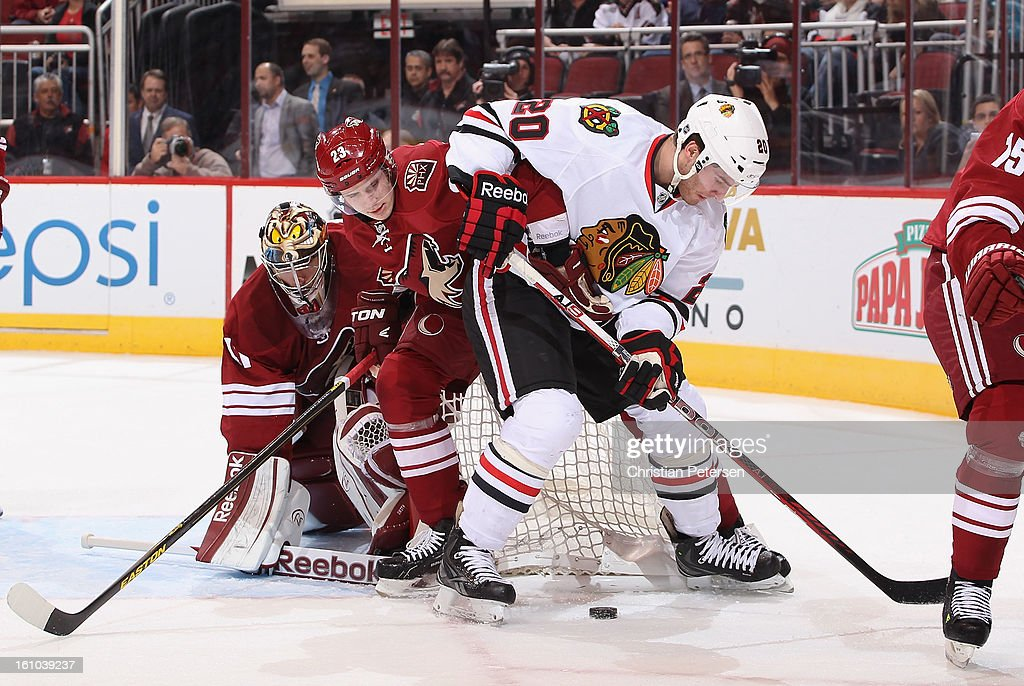 Brandon Saad #20 of the Chicago Blackhawks attempts to control the puck under pressure from <a gi-track='captionPersonalityLinkClicked' href=/galleries/search?phrase=Oliver+Ekman-Larsson&family=editorial&specificpeople=5894618 ng-click='$event.stopPropagation()'>Oliver Ekman-Larsson</a> #23 of the Phoenix Coyotes during the NHL game at Jobing.com Arena on February 7, 2013 in Glendale, Arizona. The Blackhawks defeated the Coyotes 6-2.