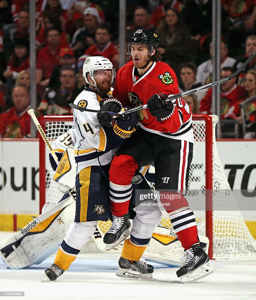Brandon Saad #20 of the Chicago Blackhawks collides with Ryan Ellis #4 of the Nashville Predators as the puck hits him in the leg in Game Four of the Western Conference Quarterfinals during the 2015 NHL Stanley Cup Playoffs at the United Center on April 21, 2015 in Chicago, Illinois.