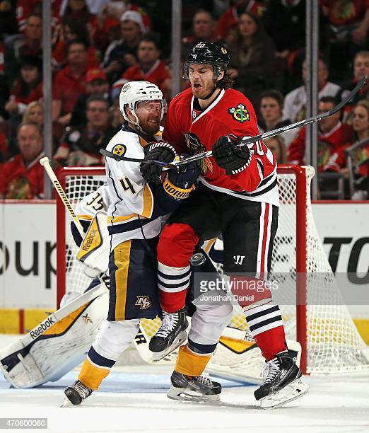 Brandon Saad of the Chicago Blackhawks collides with Ryan Ellis of the Nashville Predators as the puck hits him in the leg in Game Four of the...