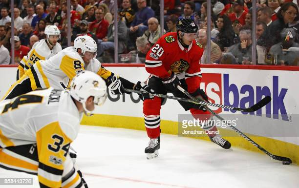 Brandon Saad of the Chicago Blackhawks digs the puck out of the corner surronded by Tom Kuhnhackl Brian Dumoulin and Kris Letang of the Pittsburgh...
