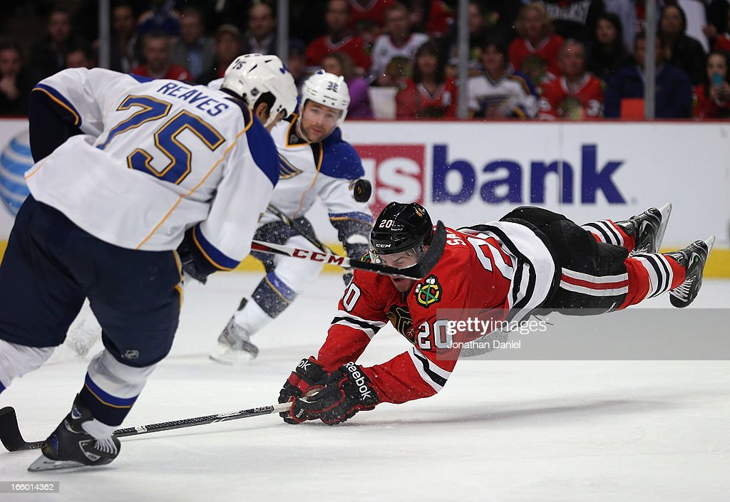 <a gi-track='captionPersonalityLinkClicked' href=/galleries/search?phrase=Brandon+Saad&family=editorial&specificpeople=7128385 ng-click='$event.stopPropagation()'>Brandon Saad</a> #20 of the Chicago Blackhawks dives for the puck between <a gi-track='captionPersonalityLinkClicked' href=/galleries/search?phrase=Ryan+Reaves&family=editorial&specificpeople=4601052 ng-click='$event.stopPropagation()'>Ryan Reaves</a> #75 and Chris Poter #32 of the St. Louis Blues at the United Center on April 4, 2013 in Chicago, Illinois. The Blues defeated the Blackhawks 4-3 in a shootout.