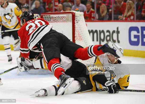 Brandon Saad of the Chicago Blackhawks falls over Brian Dumoulin of the Pittsburgh Penguins during the season opening game at the United Center on...