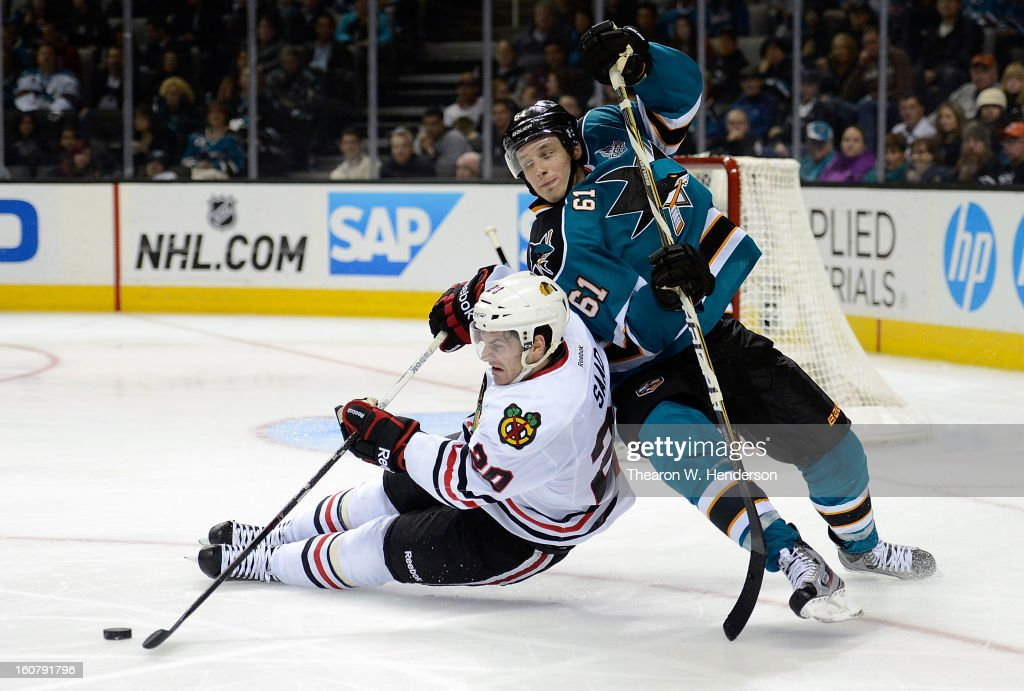 Brandon Saad #20 of the Chicago Blackhawks falls to the ice to slap the puck away from Justin Braun #61 of the San Jose Sharks in the third period at HP Pavilion on February 5, 2013 in San Jose, California. The Blackhawks won the game 5-3.