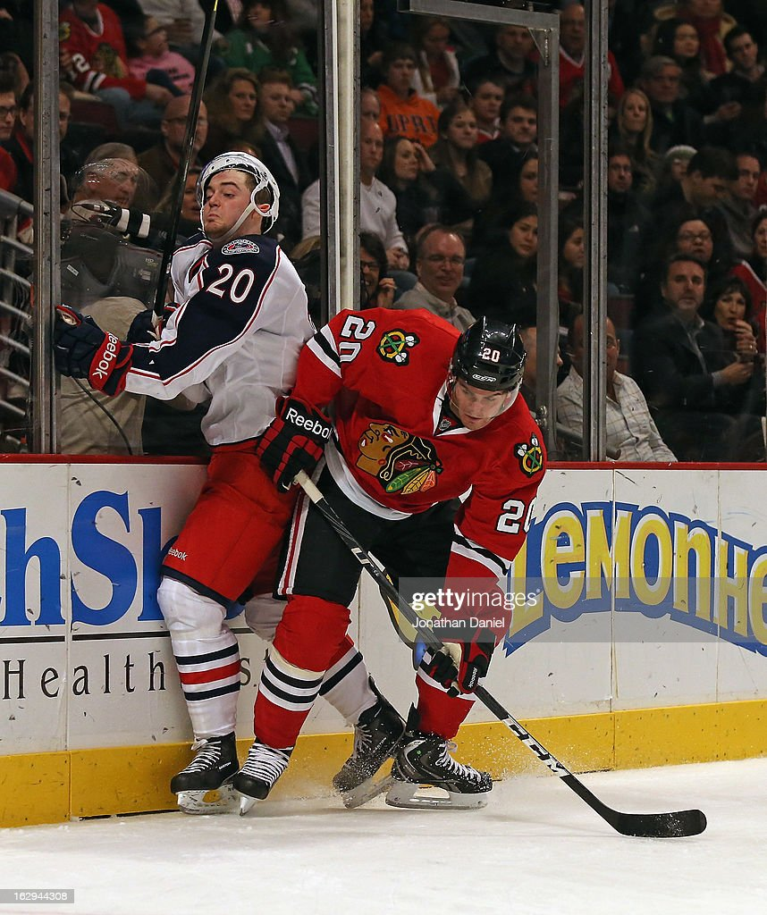 Brandon Saad #20 of the Chicago Blackhawks hip checks Tim Erixon #20 of the Columbus Blue Jackets at the United Center on March 1, 2013 in Chicago, Illinois. The Blackhawks defeated the Blue Jackets 4-3 in overtime.