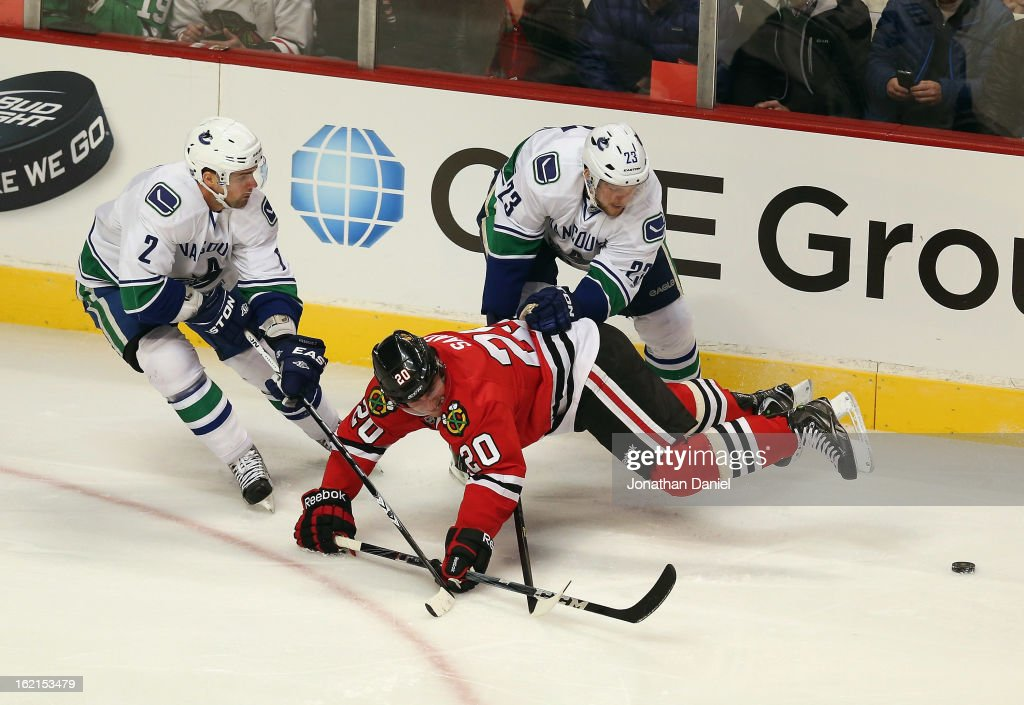 Brandon Saad #20 of the Chicago Blackhawks is knocked to the ice by <a gi-track='captionPersonalityLinkClicked' href=/galleries/search?phrase=Alexander+Edler&family=editorial&specificpeople=882987 ng-click='$event.stopPropagation()'>Alexander Edler</a> #23 and <a gi-track='captionPersonalityLinkClicked' href=/galleries/search?phrase=Dan+Hamhuis&family=editorial&specificpeople=204213 ng-click='$event.stopPropagation()'>Dan Hamhuis</a> #2 of the Vancouver Canucks at the United Center on February 19, 2013 in Chicago, Illinois.