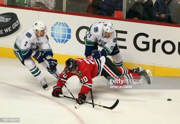 Brandon Saad of the Chicago Blackhawks is knocked to the ice by Alexander Edler and Dan Hamhuis of the Vancouver Canucks at the United Center on...