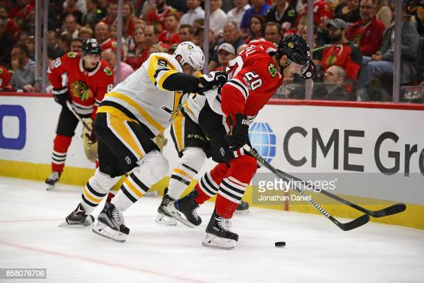 Brandon Saad of the Chicago Blackhawks is pushed by Brian Dumoulin of the Pittsburgh Penguins during the season opening game at the United Center on...