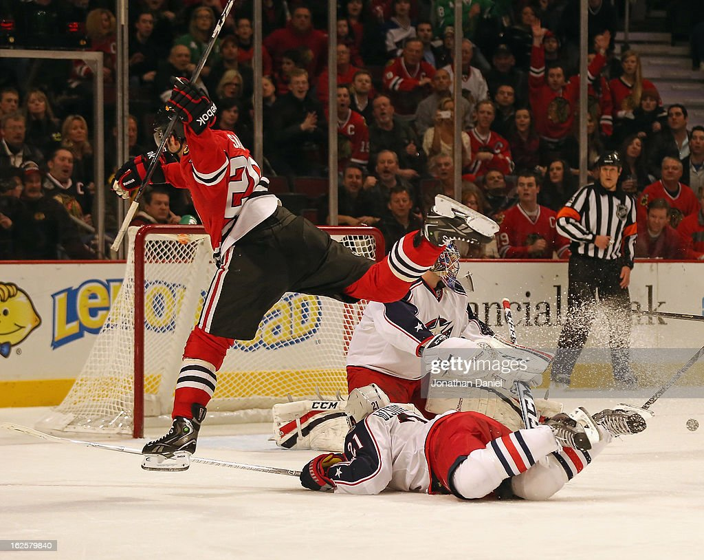 Brandon Saad of the Chicago Blackhawks leaps over James Wisniewski of the Columbus Blue Jackets at the United Center on February 24 2013 in Chicago...