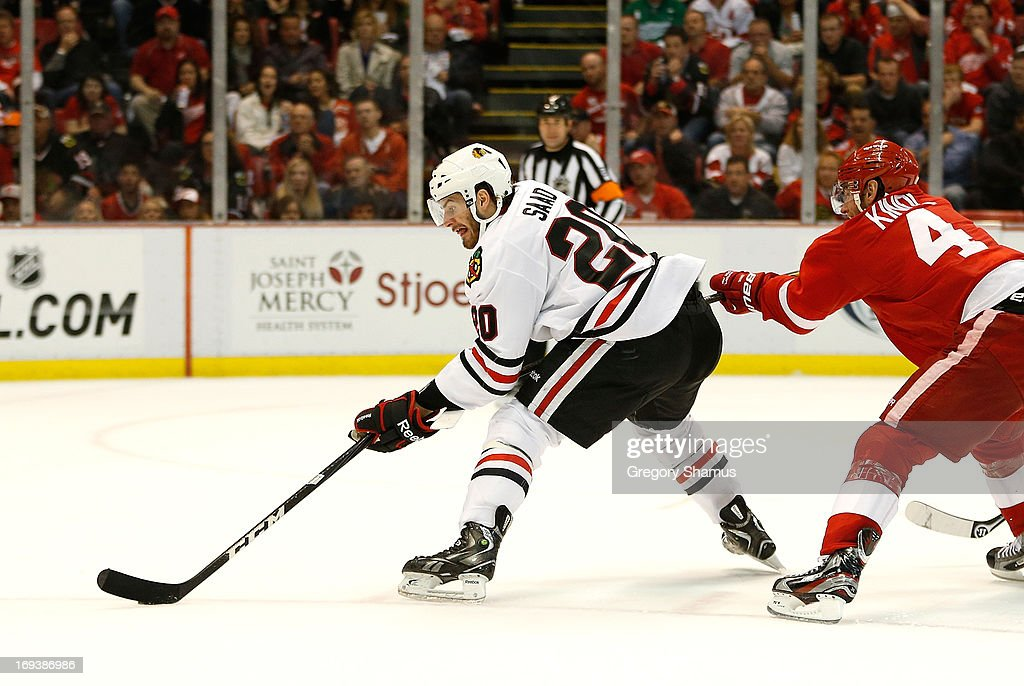 <a gi-track='captionPersonalityLinkClicked' href=/galleries/search?phrase=Brandon+Saad&family=editorial&specificpeople=7128385 ng-click='$event.stopPropagation()'>Brandon Saad</a> #20 of the Chicago Blackhawks looks to get a third period shot off while being defended by <a gi-track='captionPersonalityLinkClicked' href=/galleries/search?phrase=Jakub+Kindl&family=editorial&specificpeople=716743 ng-click='$event.stopPropagation()'>Jakub Kindl</a> #4 of the Detroit Red Wings in Game Four of the Western Conference Semifinals during the 2013 NHL Stanley Cup Playoffs at Joe Louis Arena on May 23, 2013 in Detroit, Michigan. Detroit won the game 2-0 to take a 3-1 series lead.