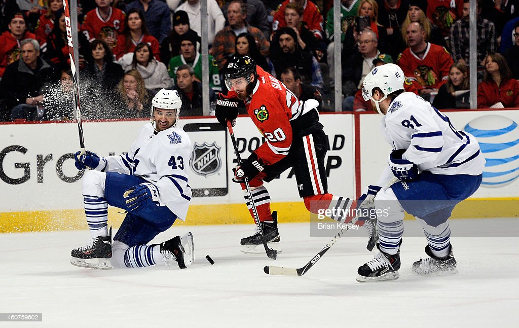 <a gi-track='captionPersonalityLinkClicked' href=/galleries/search?phrase=Brandon+Saad&family=editorial&specificpeople=7128385 ng-click='$event.stopPropagation()'>Brandon Saad</a> #20 of the Chicago Blackhawks moves the puck as <a gi-track='captionPersonalityLinkClicked' href=/galleries/search?phrase=Nazem+Kadri&family=editorial&specificpeople=4043234 ng-click='$event.stopPropagation()'>Nazem Kadri</a> #43 of the Toronto Maple Leafs and <a gi-track='captionPersonalityLinkClicked' href=/galleries/search?phrase=Phil+Kessel&family=editorial&specificpeople=537794 ng-click='$event.stopPropagation()'>Phil Kessel</a> #81 defend during the first period at the United Center on December 21, 2014 in Chicago, Illinois.