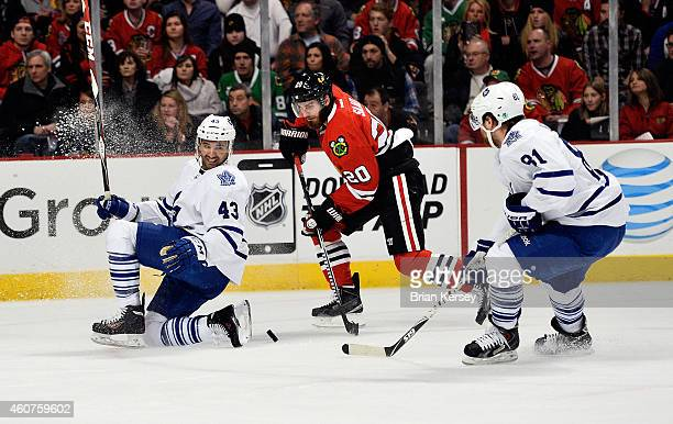 Brandon Saad of the Chicago Blackhawks moves the puck as Nazem Kadri of the Toronto Maple Leafs and Phil Kessel defend during the first period at the...