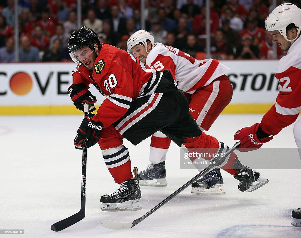 <a gi-track='captionPersonalityLinkClicked' href=/galleries/search?phrase=Brandon+Saad&family=editorial&specificpeople=7128385 ng-click='$event.stopPropagation()'>Brandon Saad</a> #20 of the Chicago Blackhawks moves up the ice chased by <a gi-track='captionPersonalityLinkClicked' href=/galleries/search?phrase=Niklas+Kronwall&family=editorial&specificpeople=220826 ng-click='$event.stopPropagation()'>Niklas Kronwall</a> #55 and <a gi-track='captionPersonalityLinkClicked' href=/galleries/search?phrase=Jonathan+Ericsson&family=editorial&specificpeople=2538498 ng-click='$event.stopPropagation()'>Jonathan Ericsson</a> #52 of the Detroit Red Wings in Game One of the Western Conference Semifinals during the 2013 NHL Stanley Cup Playoffs at the United Center on May 15, 2013 in Chicago, Illinois. The Blackhawks defeated the Red Wings 4-1.