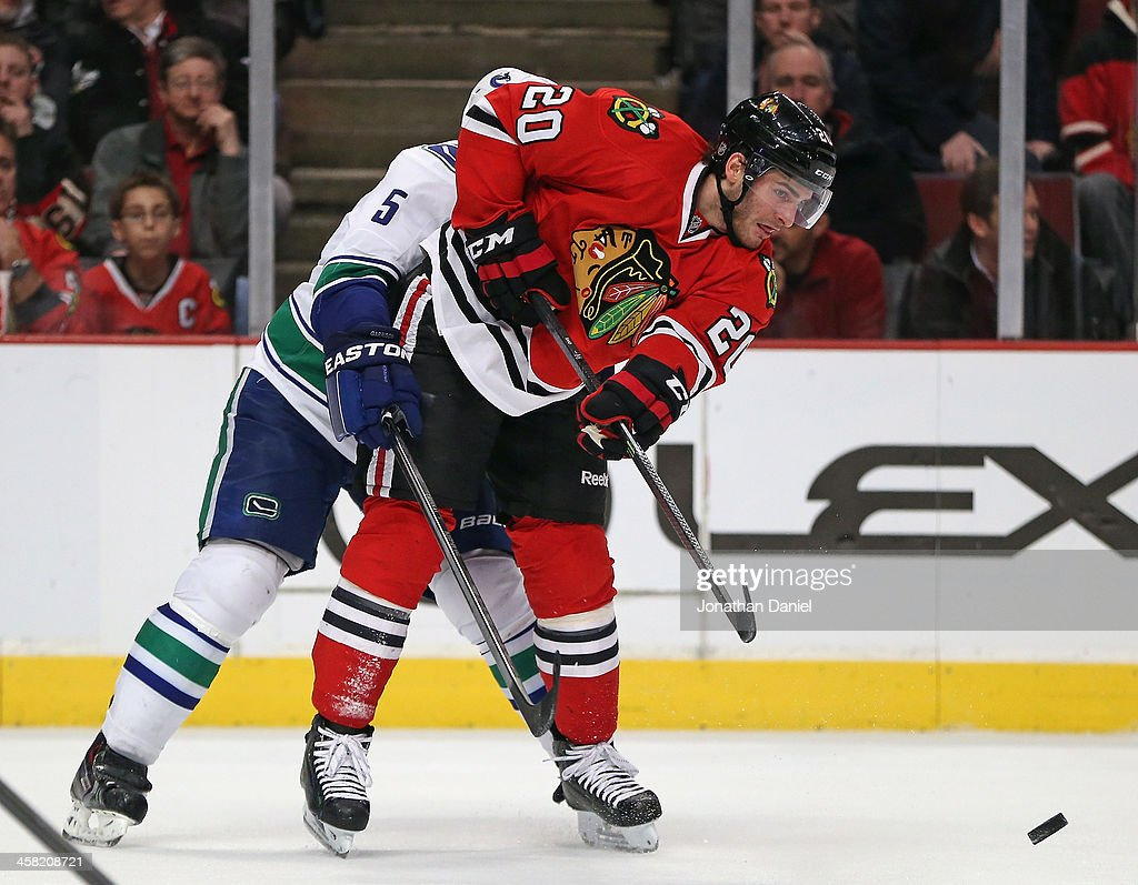 <a gi-track='captionPersonalityLinkClicked' href=/galleries/search?phrase=Brandon+Saad&family=editorial&specificpeople=7128385 ng-click='$event.stopPropagation()'>Brandon Saad</a> #20 of the Chicago Blackhawks passes as he is held by <a gi-track='captionPersonalityLinkClicked' href=/galleries/search?phrase=Jason+Garrison&family=editorial&specificpeople=2143635 ng-click='$event.stopPropagation()'>Jason Garrison</a> #5 of the Vancouver Canucks at the United Center on December 20, 2013 in Chicago, Illinois. The Canucks defeated the Blackhawks 3-2 in a shootout.