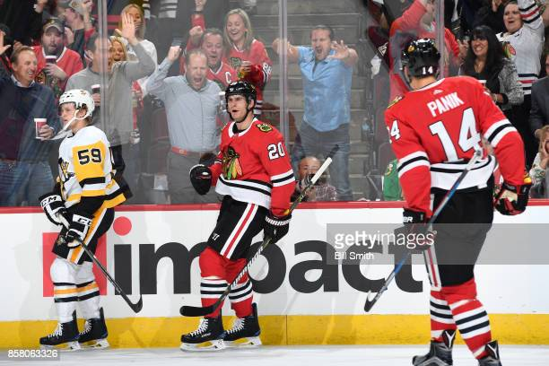 Brandon Saad of the Chicago Blackhawks reacts next to Jake Guentzel of the Pittsburgh Penguins after scoring in the first period at the United Center...