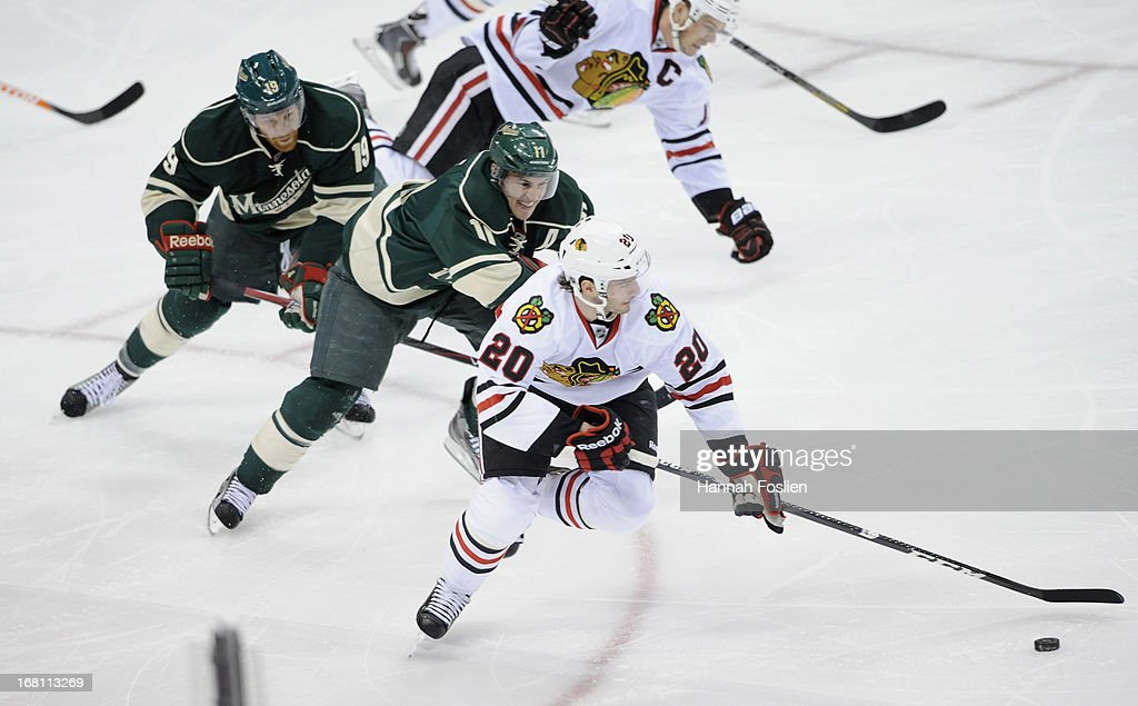 <a gi-track='captionPersonalityLinkClicked' href=/galleries/search?phrase=Brandon+Saad&family=editorial&specificpeople=7128385 ng-click='$event.stopPropagation()'>Brandon Saad</a> #20 of the Chicago Blackhawks skates the puck down the ice against <a gi-track='captionPersonalityLinkClicked' href=/galleries/search?phrase=Zach+Parise&family=editorial&specificpeople=213606 ng-click='$event.stopPropagation()'>Zach Parise</a> #11 and <a gi-track='captionPersonalityLinkClicked' href=/galleries/search?phrase=Stephane+Veilleux&family=editorial&specificpeople=217366 ng-click='$event.stopPropagation()'>Stephane Veilleux</a> #19 of the Minnesota Wild during the first period of Game Three of the Western Conference Quarterfinals during the 2013 NHL Stanley Cup Playoffs at Xcel Energy Center on May 5, 2013 in St Paul, Minnesota.