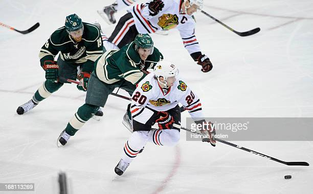 Brandon Saad of the Chicago Blackhawks skates the puck down the ice against Zach Parise and Stephane Veilleux of the Minnesota Wild during the first...