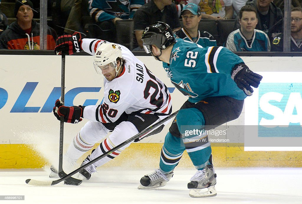 Brandon Saad #20 of the Chicago Blackhawks skates with control of the puck keeping it away from Matt Irwin #52 of the San Jose Sharks during the first period at SAP Center on February 1, 2014 in San Jose, California.