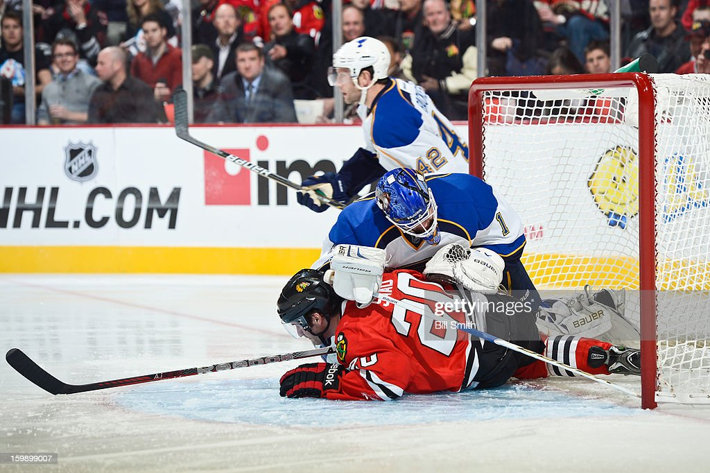 Brandon Saad #20 of the Chicago Blackhawks slides into goalie Brian Elliott #1 of the St. Louis Blues during the NHL game on January 22, 2013 at the United Center in Chicago, Illinois.