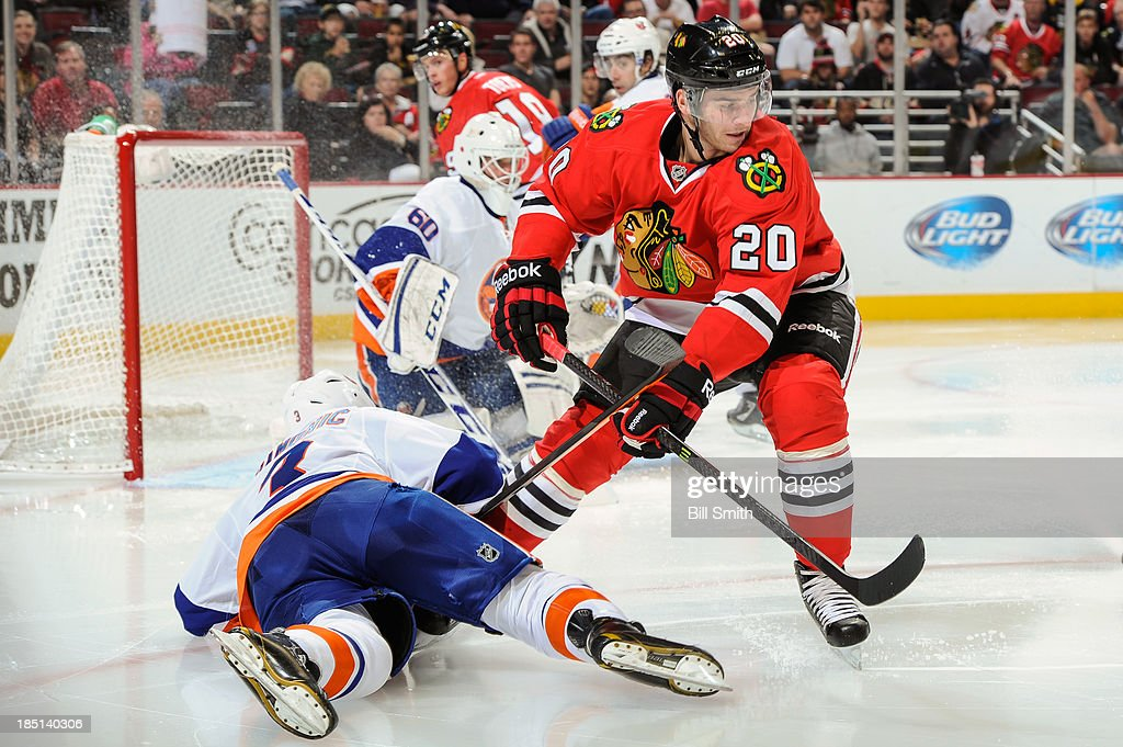<a gi-track='captionPersonalityLinkClicked' href=/galleries/search?phrase=Brandon+Saad&family=editorial&specificpeople=7128385 ng-click='$event.stopPropagation()'>Brandon Saad</a> #20 of the Chicago Blackhawks slides into <a gi-track='captionPersonalityLinkClicked' href=/galleries/search?phrase=Travis+Hamonic&family=editorial&specificpeople=4605791 ng-click='$event.stopPropagation()'>Travis Hamonic</a> #3 of the New York Islanders during the NHL game on October 11, 2013 at the United Center in Chicago, Illinois.