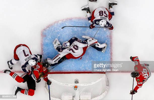 Brandon Saad of the Chicago Blackhawks slides on the ice in front of Jack Johnson of the Columbus Blue Jackets after scoring on goalie Joonas...