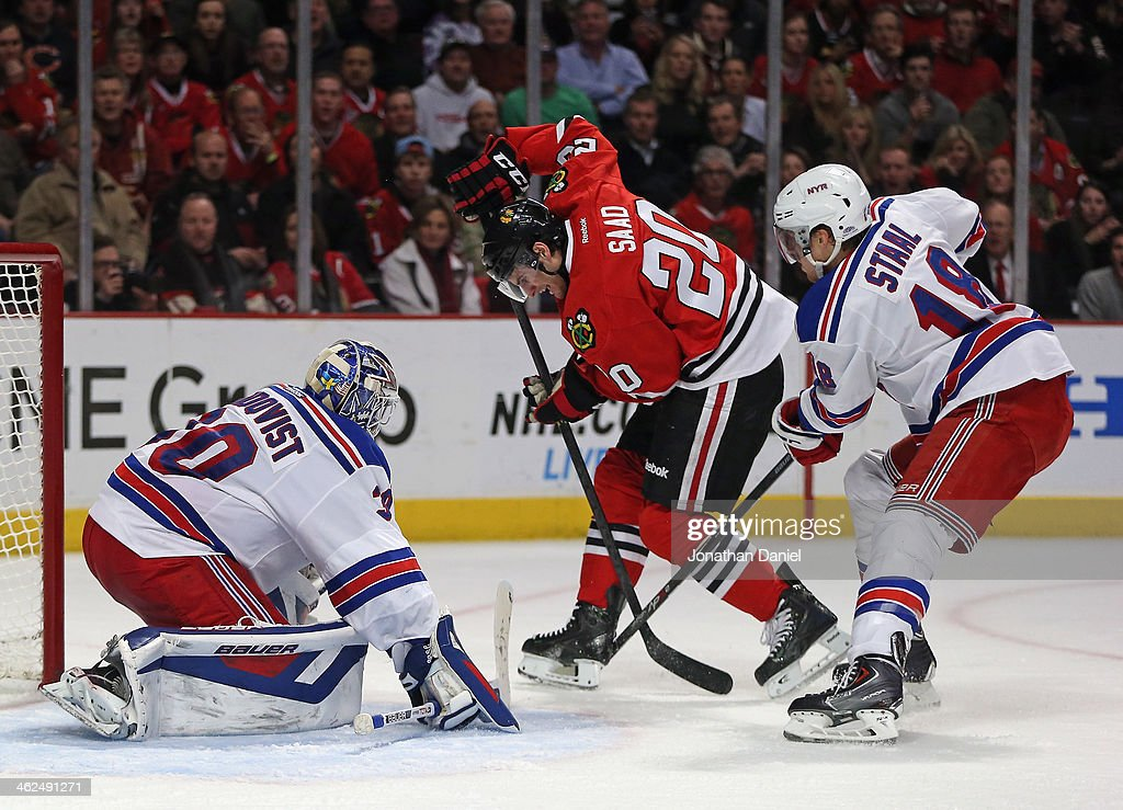 <a gi-track='captionPersonalityLinkClicked' href=/galleries/search?phrase=Brandon+Saad&family=editorial&specificpeople=7128385 ng-click='$event.stopPropagation()'>Brandon Saad</a> #20 of the Chicago Blackhawks tries to shoot between Henrik Lindqvist #30 (L) and <a gi-track='captionPersonalityLinkClicked' href=/galleries/search?phrase=Marc+Staal&family=editorial&specificpeople=3809026 ng-click='$event.stopPropagation()'>Marc Staal</a> #18 of the New York Rangers at the United Center on January 8, 2014 in Chicago, Illinois. The Rangers defeated the Blackhawks 3-2.