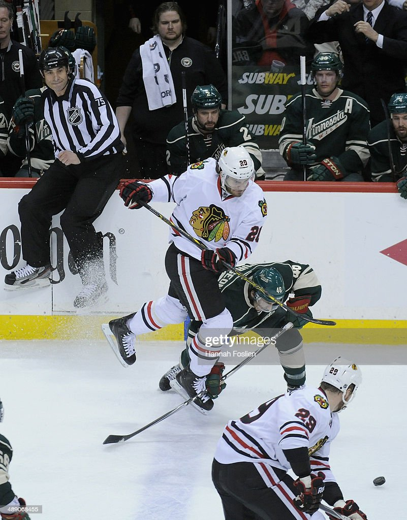 Brandon Saad #20 of the Chicago Blackhawks trips on a the stick of Jared Spurgeon #46 of the Minnesota Wild during the first period in Game Four of the Second Round of the 2014 NHL Stanley Cup Playoffs on May 9, 2014 at Xcel Energy Center in St Paul, Minnesota.