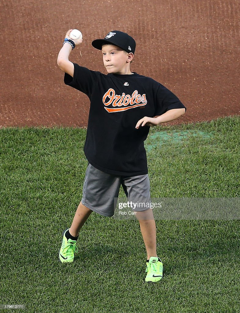 Brandon Schneider, 10, the son of fallen Baltimore County Police officer Jason Schneider who was killed in the line of duty last month, throws out the ceremonial first pitch before the start of the Baltimore Orioles and Chicago White Sox game at Oriole Park at Camden Yards on September 5, 2013 in Baltimore, Maryland.