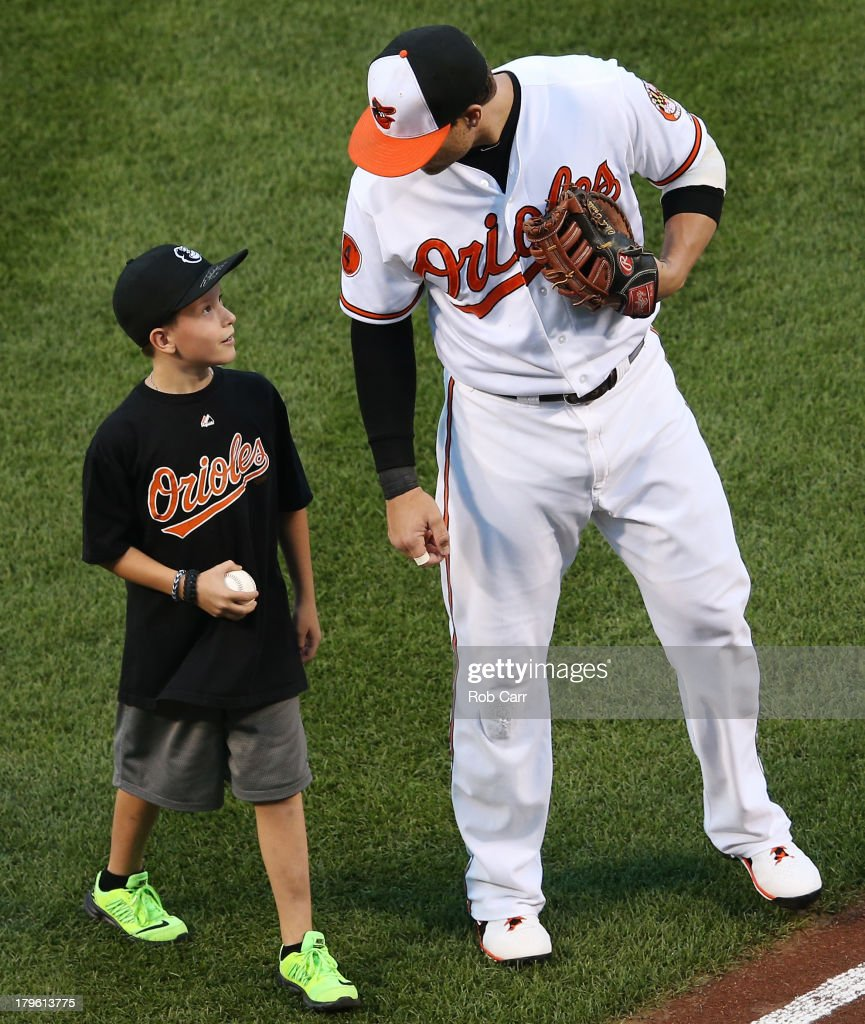 Brandon Schneider, 10, the son of fallen Baltimore County Police officer Jason Schneider who was killed in the line of duty last month, talks with Chris Davis #19 of the Baltimore Orioles after throwing out the ceremonial first pitch before the start of the Orioles and Chicago White Sox game at Oriole Park at Camden Yards on September 5, 2013 in Baltimore, Maryland.