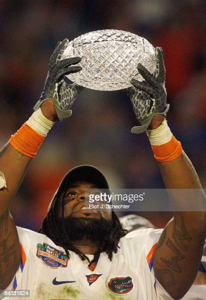 Brandon Spikes of the Florida Gators holds up the winning trophy after the FedEx BCS National Championship Game against the Oklahoma Sooners at...