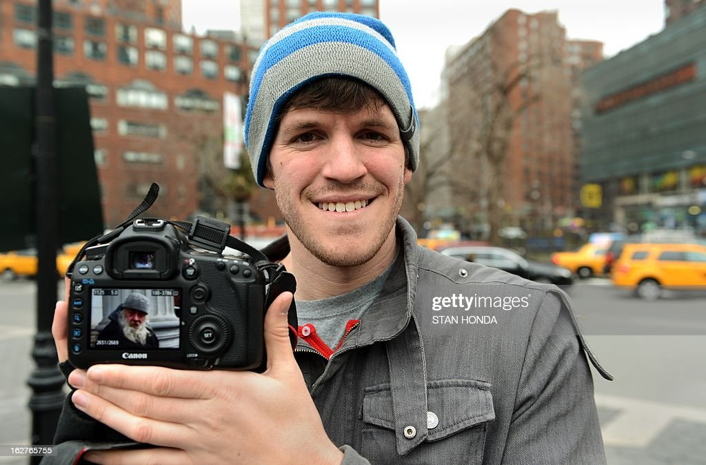 Brandon Stanton (L), creator of the Humans of New York blog, shows an image he took of a man named Carl February 22, 2013 across the street from Union Square in New York. Some like New York's skyscrapers, bridges, his energy, taxis or lights. But Brandon Stanton has set himself another challenge: photograph of 10,000 inhabitants for a blog now famous 'Humans of New York.' In two years, he has photographed 5,000 New Yorkers, children leaving school, tramps, fashionistas, New York with a bouquet of tulips, old lady with a cane, municipal employees, etc. And nearly 560,000 fans now follow his Facebook page.AFP PHOTO/Stan HONDA