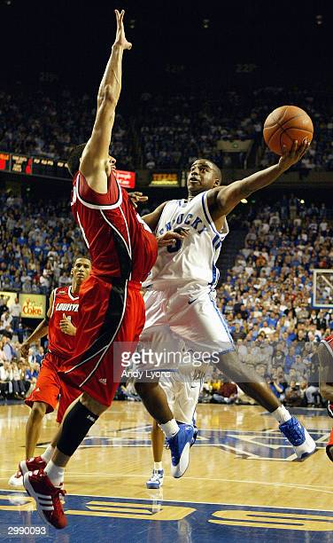 Brandon Stockton of the Kentucky Wildcats shoots over Luke Whitehead of the Louisville Cardinals during the game on December 27 2003 at Rupp Arena in...