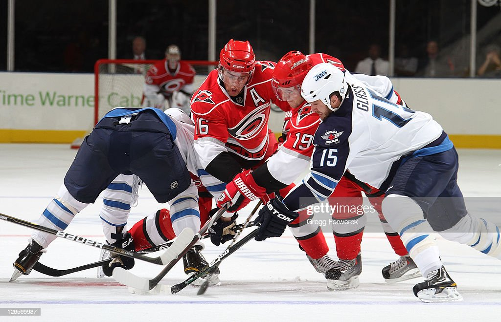Brandon Sutter #16 and <a gi-track='captionPersonalityLinkClicked' href=/galleries/search?phrase=Jiri+Tlusty&family=editorial&specificpeople=543236 ng-click='$event.stopPropagation()'>Jiri Tlusty</a> #19 of the Carolina Hurricanes battle for the puck against <a gi-track='captionPersonalityLinkClicked' href=/galleries/search?phrase=Tanner+Glass&family=editorial&specificpeople=4596666 ng-click='$event.stopPropagation()'>Tanner Glass</a> #15 of the Winnipeg Jets during an NHL preseason game on September 25, 2011 at Time Warner Arena in Charlotte, North Carolina.