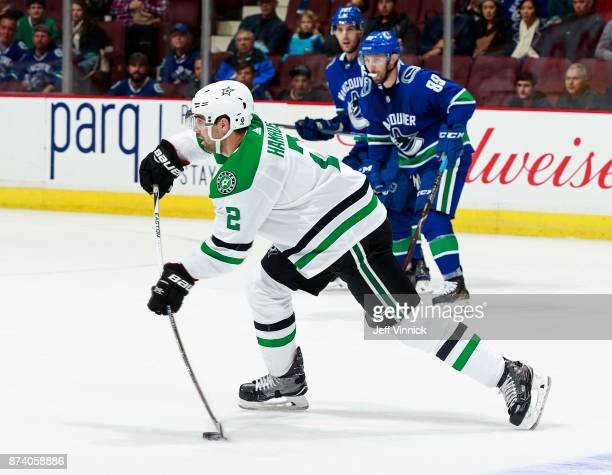 Brandon Sutter and Sam Gagner of the Vancouver Canucks look on as Dan Hamhuis of the Dallas Stars passes the puck up ice during their NHL game at...