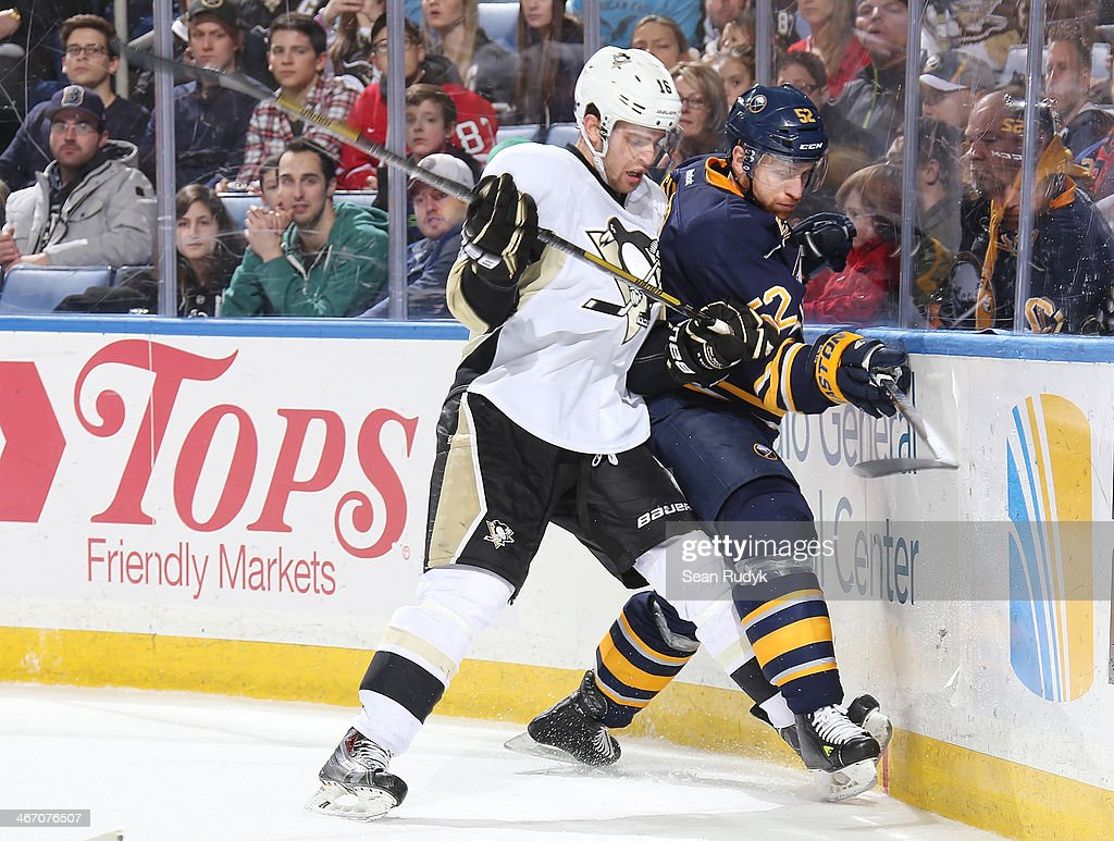 Brandon Sutter #16 of the Pittsburgh Penguins checks Alexander Sulzer #52 of the Buffalo Sabres into the end boards at First Niagara Center on February 5, 2014 in Buffalo, New York.