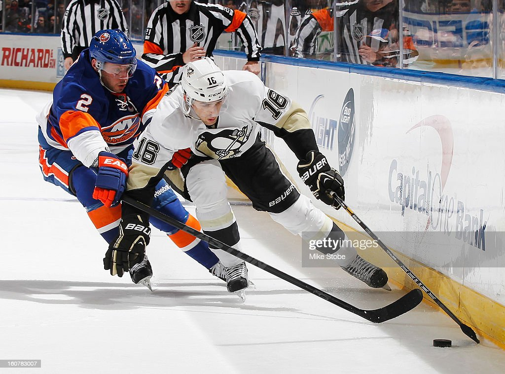 Brandon Sutter #16 of the Pittsburgh Penguins controls the puck in front of Mark Streit #2 of the New York Islanders at Nassau Veterans Memorial Coliseum on Febuary 5, 2013 in Uniondale, New York.