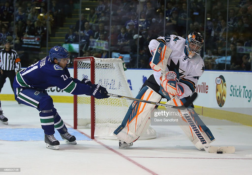 Brandon Sutter of the Vancouver Canucks stick checks Aaron Dell of the San Jose Sharks during Day 3 of NHL Kraft Hockeyville at the Q Centre on...