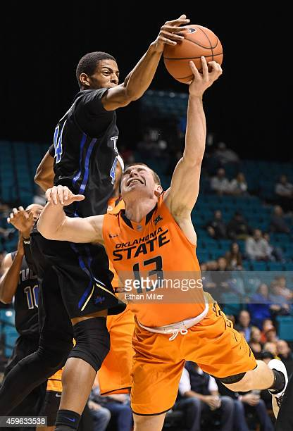 Brandon Swannegan of the Tulsa Golden Hurricane blocks a shot by Phil Forte III of the Oklahoma State Cowboys during the championship game of the...