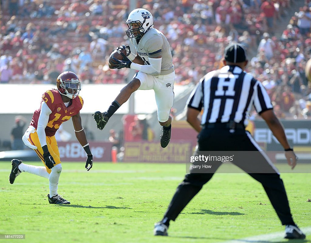 Brandon Swindall #11 of the Utah State Aggies makes a catch for a first down in front of Kevon Seymour #13 of the USC Trojans during a 17-14 Trojan win at the Los Angeles Memorial Coliseum on September 21, 2013 in Los Angeles, California.